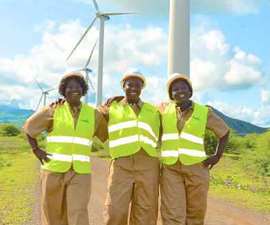 three women wearing safety vests and helmets standing in front of wind turbines
